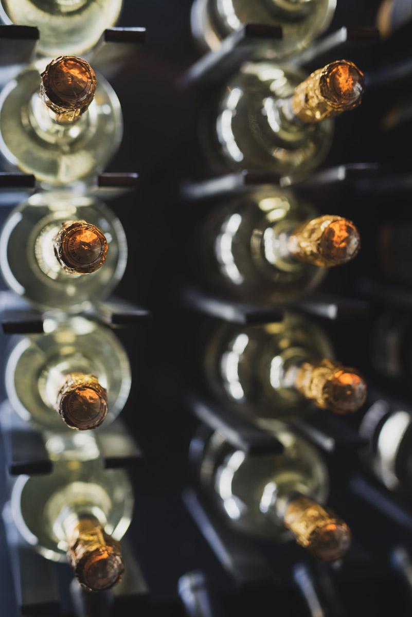 Bottiglie di vino pregiato nell'ingresso Le Boutique Luxury Resort il B&B a Fiumicino in Via della Torre Clementina 80
