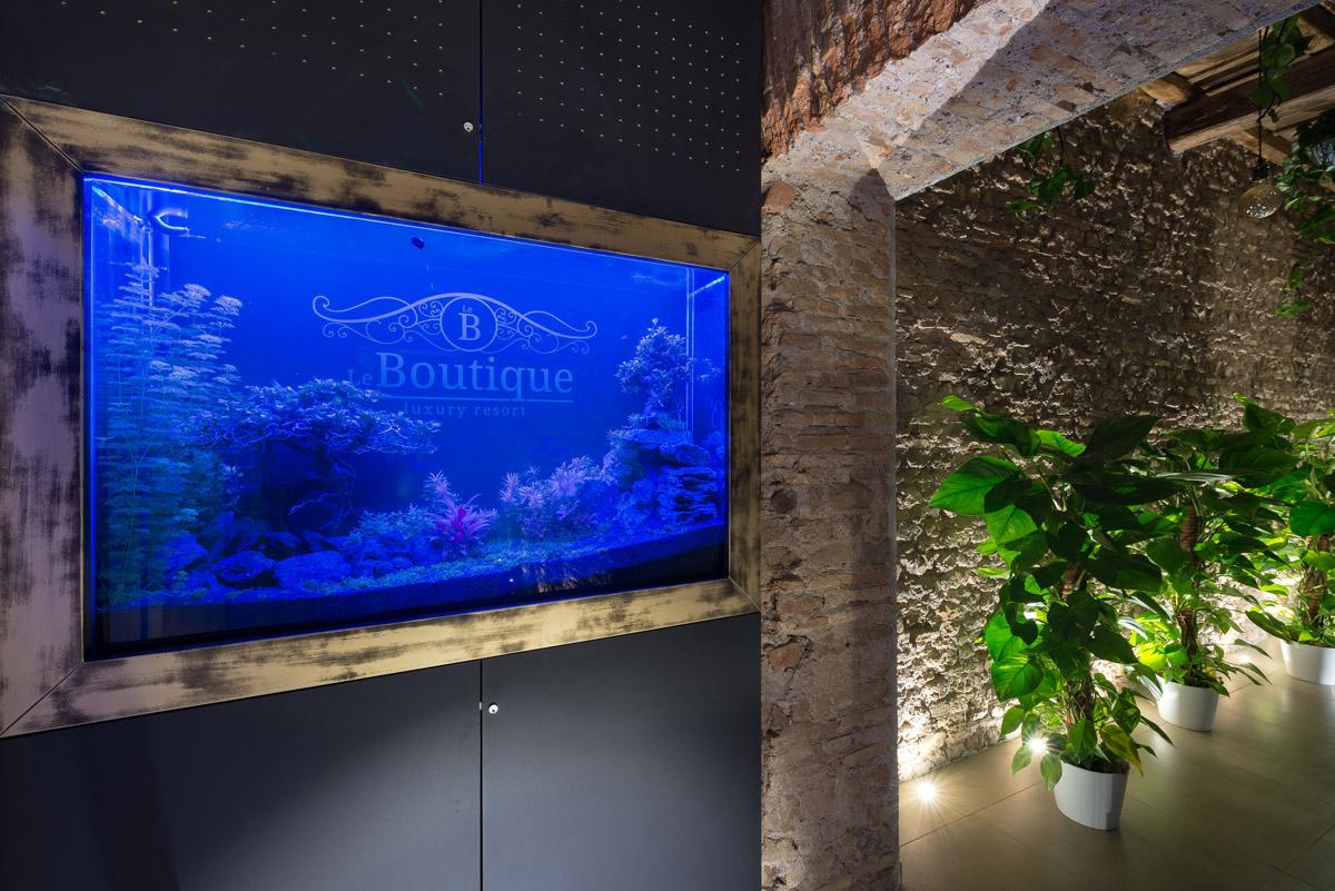 Il nostro acquario con il logo Le Boutique Luxury Resort e il corridoio con mura ottocentesche restaurate